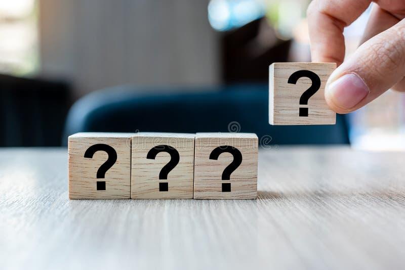 Geschäftsmannhand, die Fragezeichen hält? Wort mit hölzernem Würfelblock FAQ-Frequenz stellte Fragen, Antwort, Q&A, stockfotografie