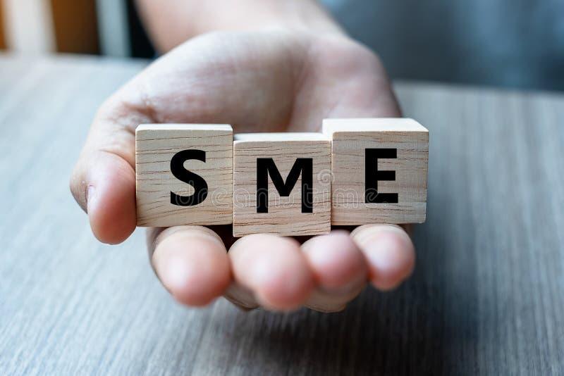 Geschäftsmannhand, die hölzernen Würfel mit SME-Text kleinem Mittelbetrieb auf Tabellenhintergrund hält Finanziell, vermarktend u stockbilder