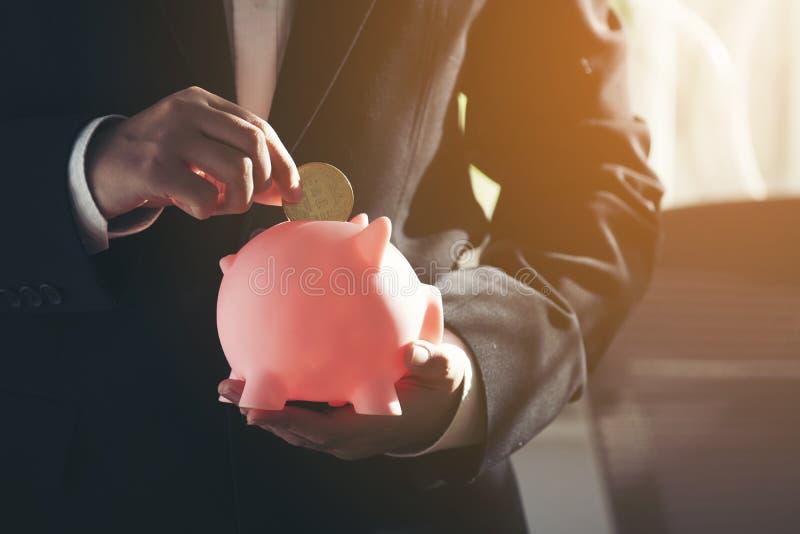 Geschäftsmannhand, die Münze in Sparschwein setzt stockbilder