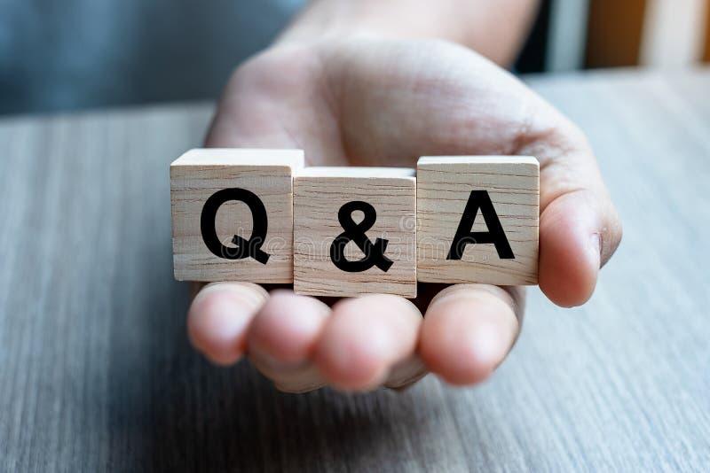 Geschäftsmannhand, die Q&A-Wort mit hölzernem Würfelblock hält FAQ Frequenz bat Fragen, beantworten Sie, fragen Sie u. bitten Sie stockbild