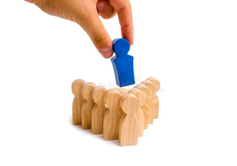 Geschäftsmannhand setzt den Führer in die Mitte einer Gruppe von Personen der Pfeilbildung auf einen weißen Hintergrund ein Schac lizenzfreies stockfoto