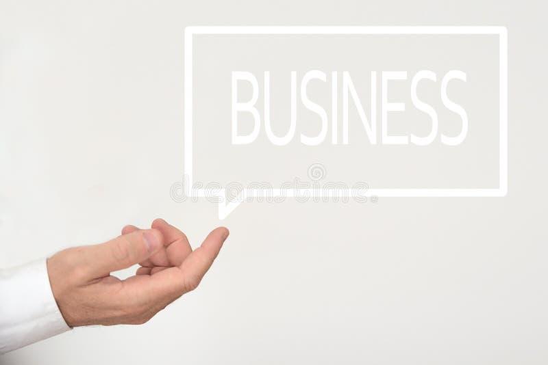 Geschäftsmannhand und eine Rede sprudeln mit dem Wort GESCHÄFT herein stockfotografie
