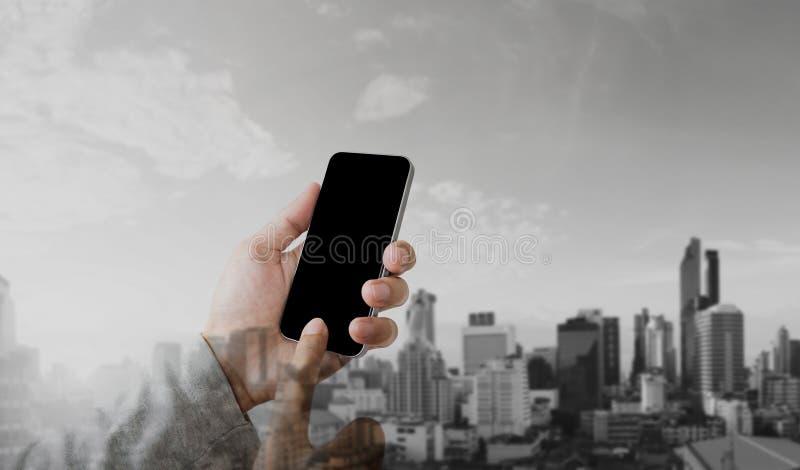 Geschäftsmannhand unter Verwendung des intelligenten Mobiltelefons mit modernem Stadthintergrund der Doppelbelichtung, leerer sch lizenzfreies stockbild