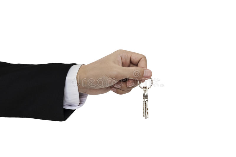 Geschäftsmannhand, welche die Schlüssel, lokalisiert auf weißem Hintergrund hält stockbild