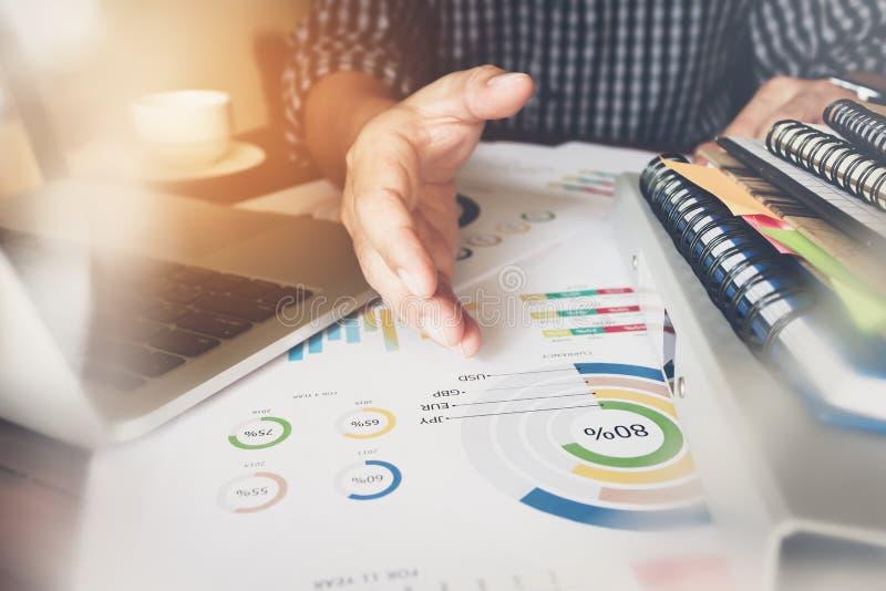 Geschäftsmannhandarbeitslaptop auf hölzernem Schreibtisch, benutzen den Begleitungsartikel in der Finanzierung lizenzfreies stockbild