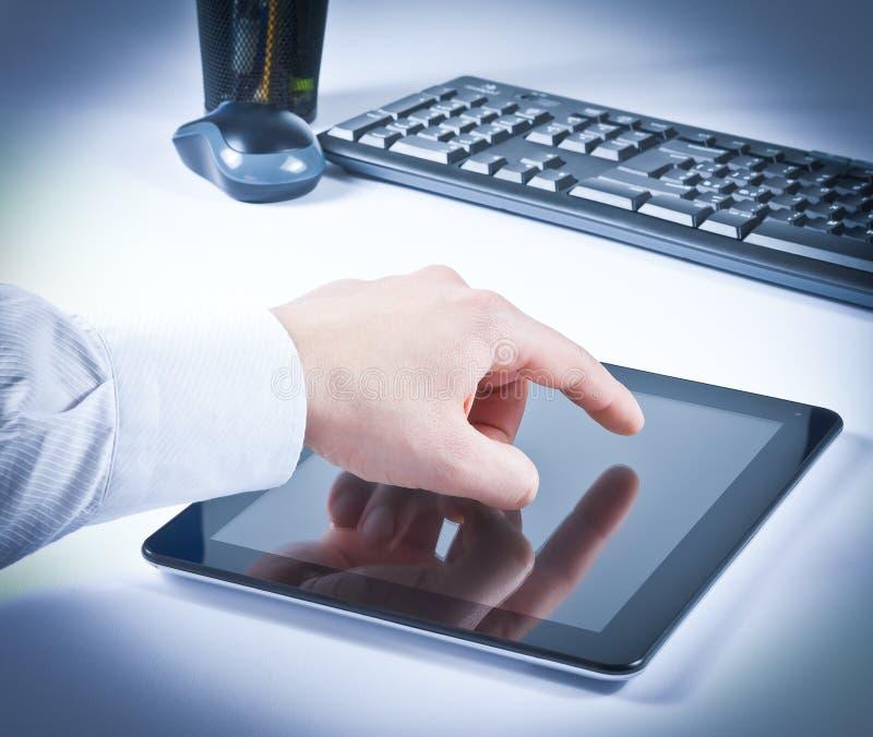 Geschäftsmannhandnotentabletten-PC im Büro stockfoto