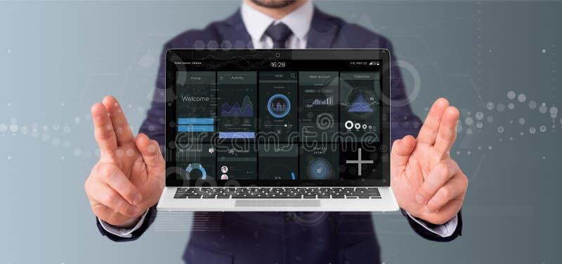 Geschäftsmannholding Laptop mit Schnittstellendaten des gewerblichen Benutzers bezüglich des Schirmes lokalisiert auf einem Hinte lizenzfreie stockfotos