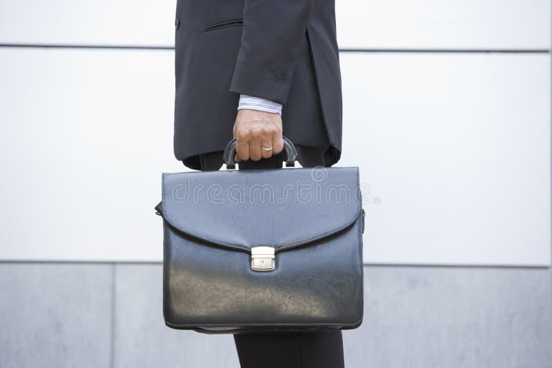Geschäftsmannholdingaktenkoffer draußen lizenzfreie stockfotografie