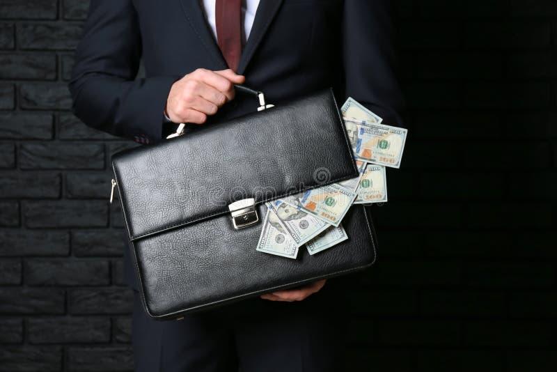 Geschäftsmannholdingaktenkoffer mit Dollarbanknoten auf dunklem Hintergrund Dollarbanknoten im Umschlag getrennt auf Wei? lizenzfreies stockfoto