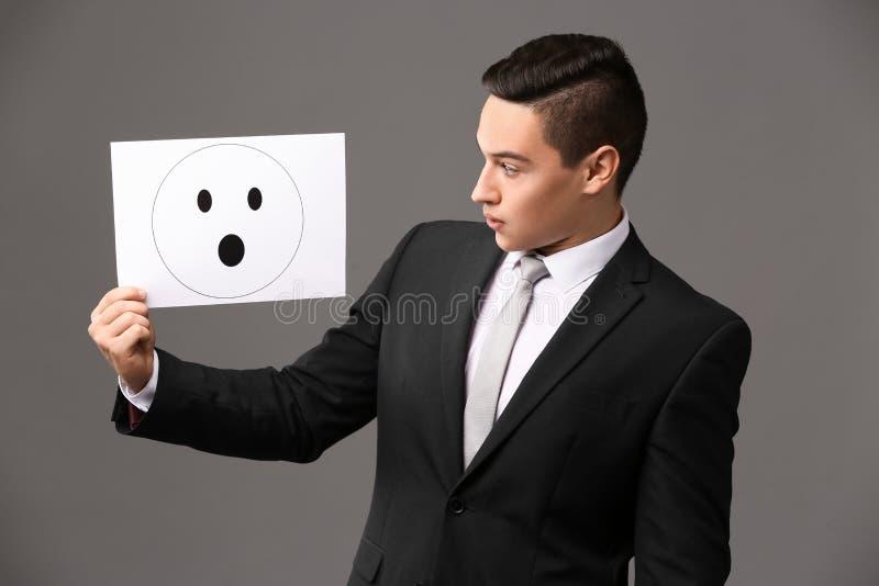 Geschäftsmannholdingblatt papier mit gezogenem Emoticon auf grauem Hintergrund lizenzfreie stockbilder