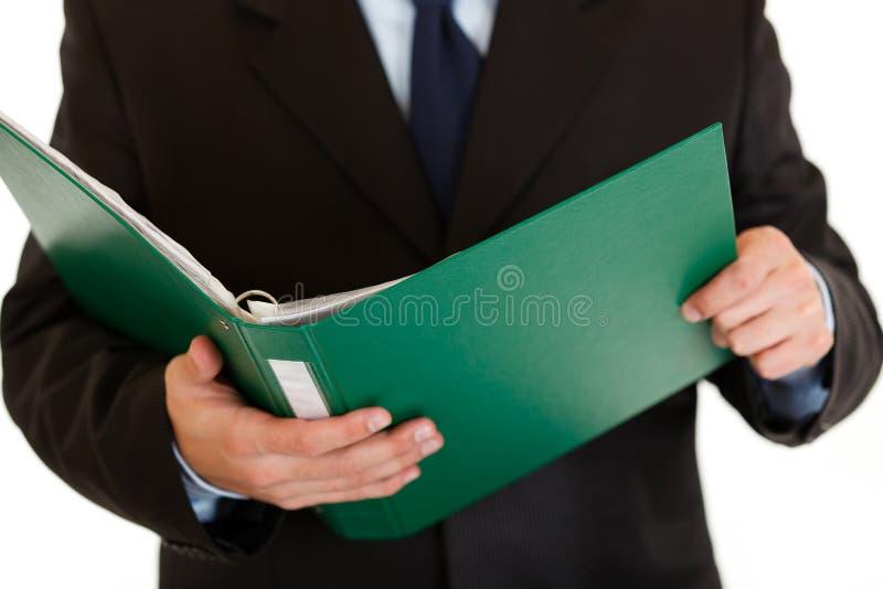 Geschäftsmannholdingfaltblatt mit Dokumenten. Nahaufnahme lizenzfreie stockfotografie