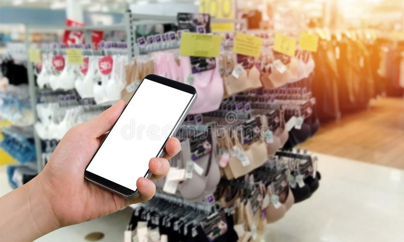 Geschäftsmannholdingleerer bildschirm für Text auf Smartphone, Mobile, Handy mit undeutlichem Frauenunterwäsche-Regalhintergrund lizenzfreie stockfotos