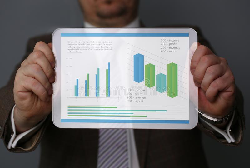 Geschäftsmannholdingtablette in den Händen mit stockbilder