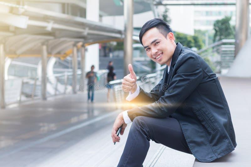 Geschäftsmannlächeln und -verpflichtung gegenüber dem Erfolg, der auf sta sitzt lizenzfreie stockfotografie