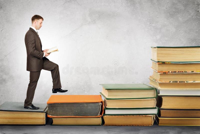 Geschäftsmannlesebuch und -wege oben lizenzfreie stockbilder