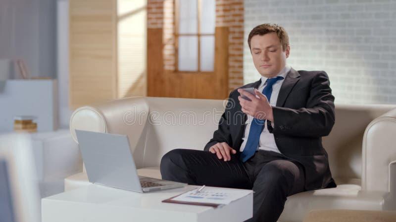 Geschäftsmannlesemitteilung im Handy, Firmenfragen entfernt lösend stockfotografie