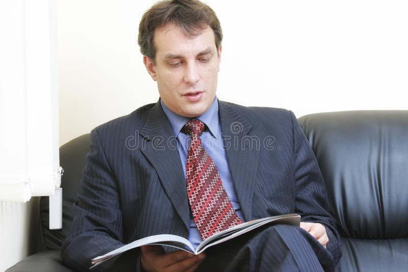 Geschäftsmannlesezeitschrift stockfoto