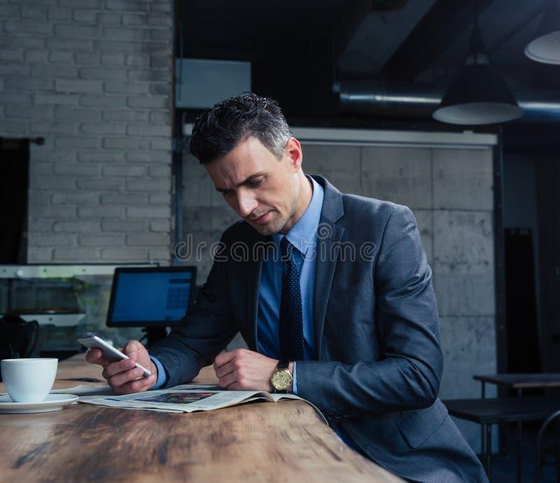 Geschäftsmannlesezeitschrift im Café stockfoto