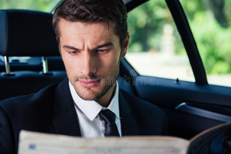 Geschäftsmannlesezeitung beim Reiten in Auto lizenzfreie stockbilder