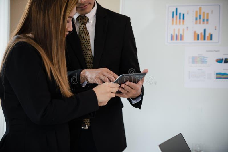 Geschäftsmannmänner und -frauen arbeiten an dem digitalen Tablet duri lizenzfreie stockbilder