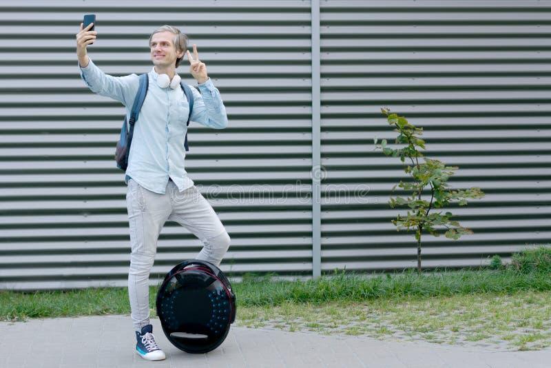 Geschäftsmannmann mit dem elektrischen Transport, der selfie tut stockfoto