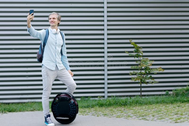 Geschäftsmannmann mit dem elektrischen Transport, der selfie tut stockbilder