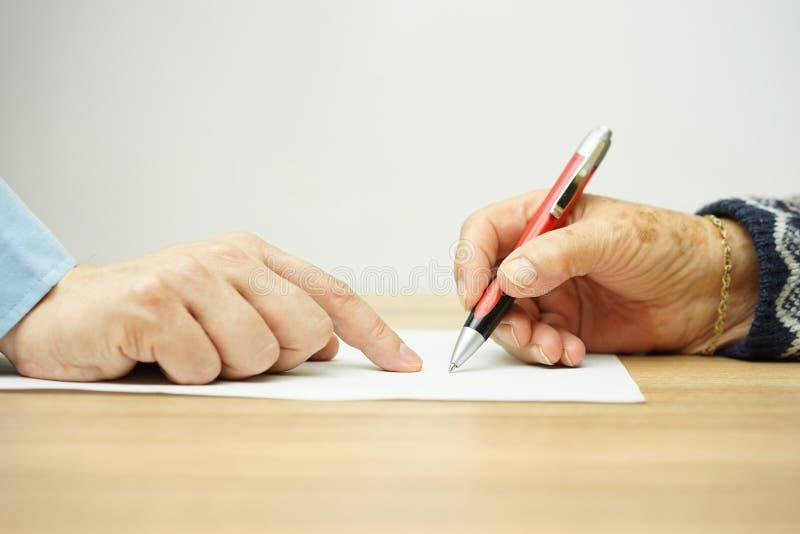 Geschäftsmannmann zeigt Senior, wo man Vertrag unterzeichnet stockbilder