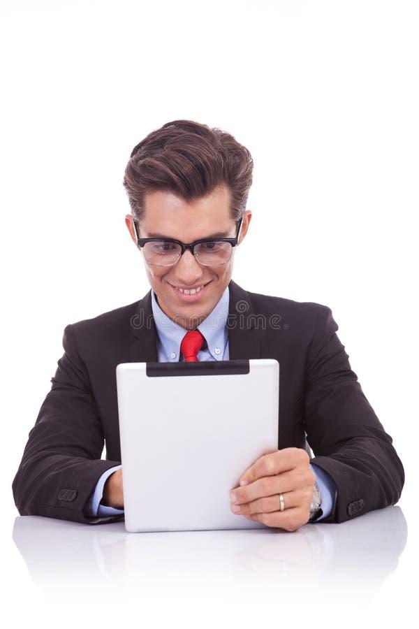 Geschäftsmannmesswert auf seiner Tablette stockbild