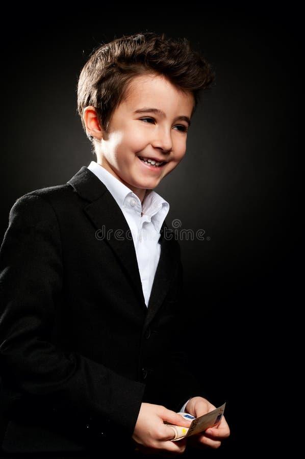 Geschäftsmannporträt des kleinen Jungen im zurückhaltenden Zählungsgeld lizenzfreie stockfotos