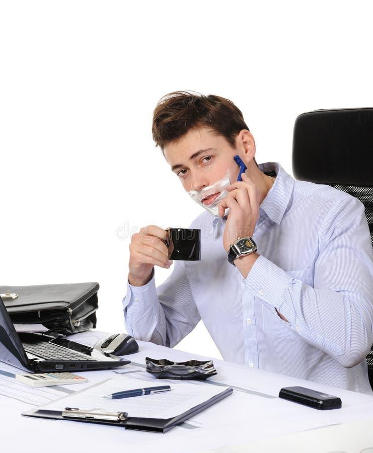 Geschäftsmannrasuren an dem Arbeitsplatz lizenzfreies stockfoto