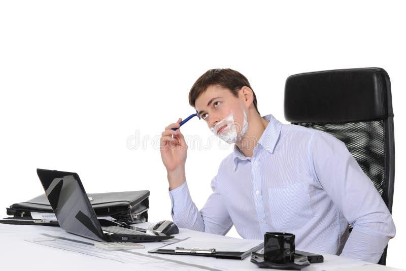 Geschäftsmannrasuren an dem Arbeitsplatz lizenzfreie stockfotografie