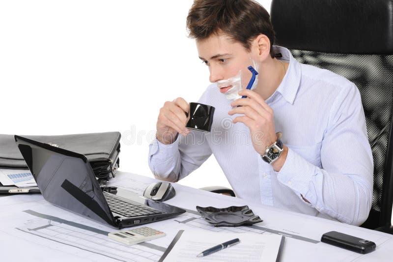 Geschäftsmannrasuren an dem Arbeitsplatz lizenzfreie stockbilder