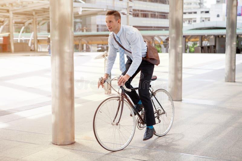 Geschäftsmannreitfahrrad, zum an städtischer Straße am Morgen zu arbeiten Transport und gesundes lizenzfreie stockfotos