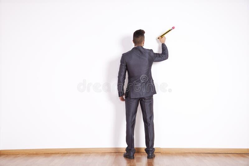 Geschäftsmannschreiben an der Bürowand stockbild
