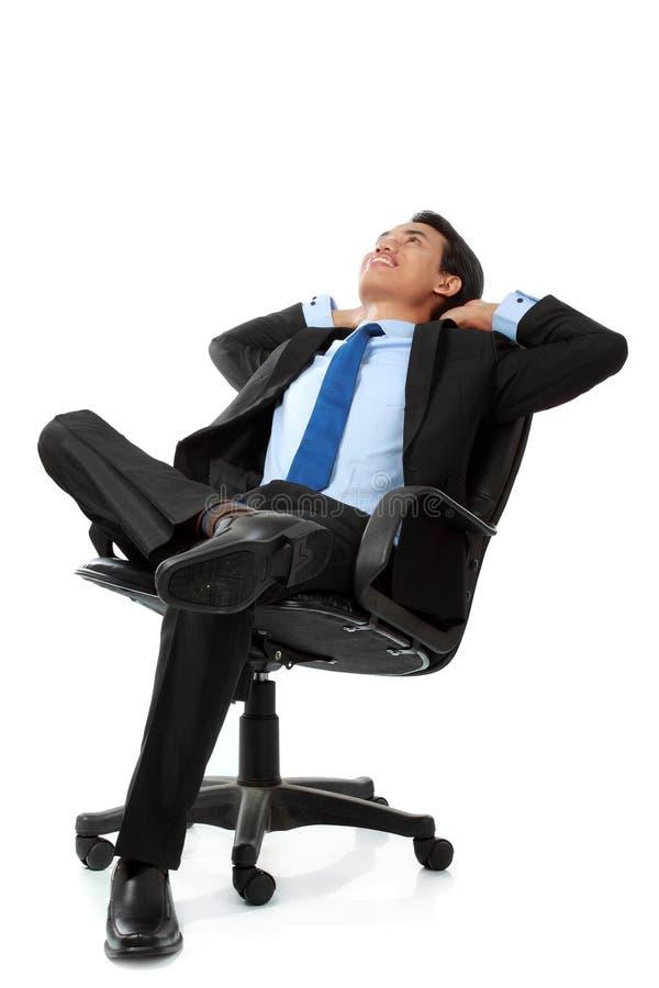 Geschäftsmannsitzen und Entspannung auf Stuhl stockfotografie