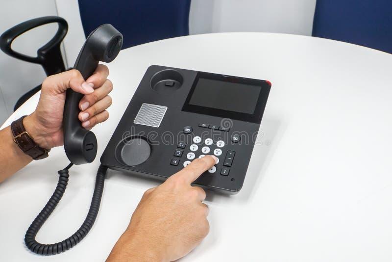 Geschäftsmannskala an IP-Telefon, das zu den Kunden ausruft lizenzfreie stockfotografie
