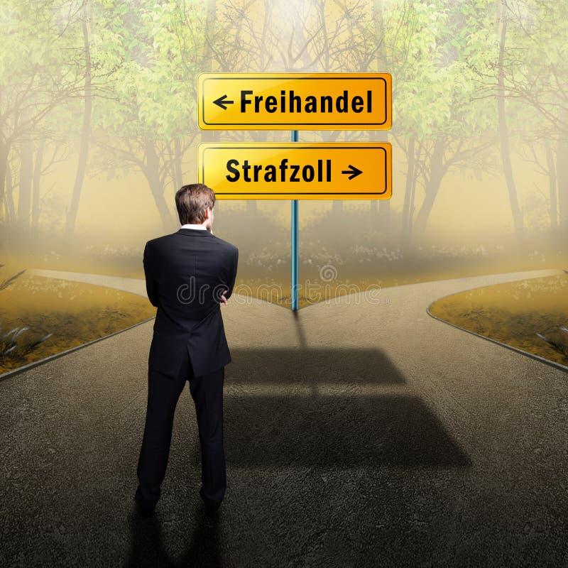 Geschäftsmannstellung an einer Kreuzung müssend zwischen 'Freihandel 'und 'Tarif 'mit Verkehrsschildern auf Deutsch entscheiden lizenzfreie stockfotografie