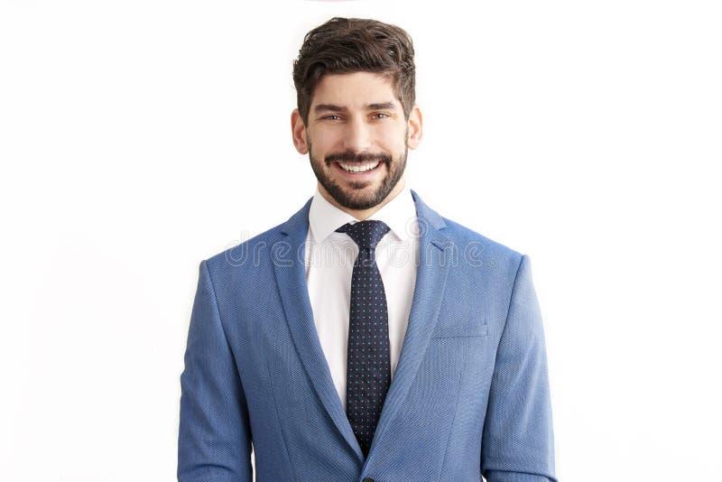 Geschäftsmannstellung an lokalisiertem weißem Hintergrund und an tragendem Anzug lizenzfreie stockfotografie