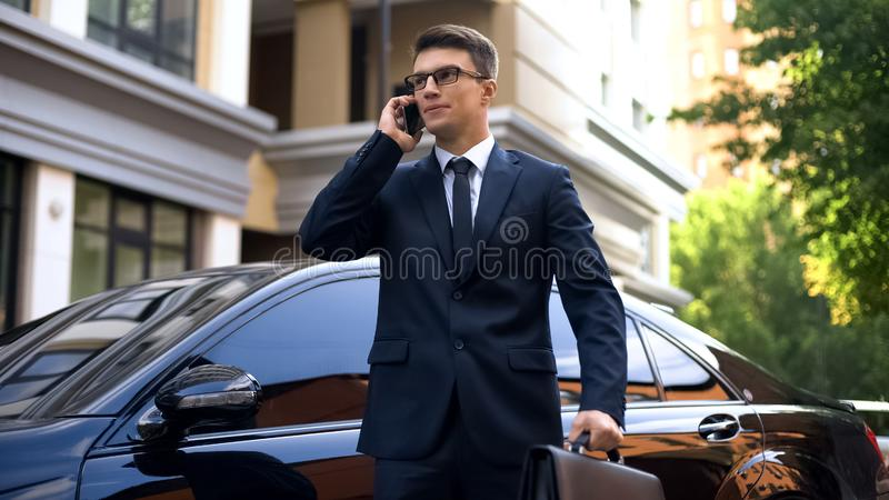 Geschäftsmannstellung nahe dem luxuriösen Auto, das auf dem Smartphone, unglücklich mit Nachrichten spricht lizenzfreies stockfoto