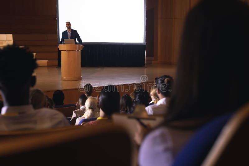 Geschäftsmannstellung um das Podium und die geben Rede vor Publikum im Auditorium stockbild