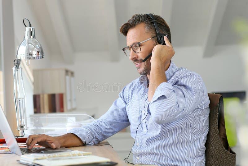 Geschäftsmanntelearbeit mit Kopfhörer auf Laptop lizenzfreie stockfotos