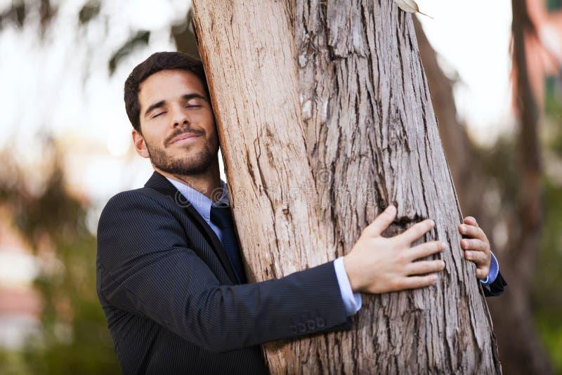 Geschäftsmannumarmung ein Baumstamm lizenzfreie stockfotos