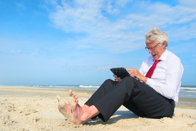 Geschäftsmannumkippen, das an Tablette am Strand arbeitet lizenzfreie stockbilder