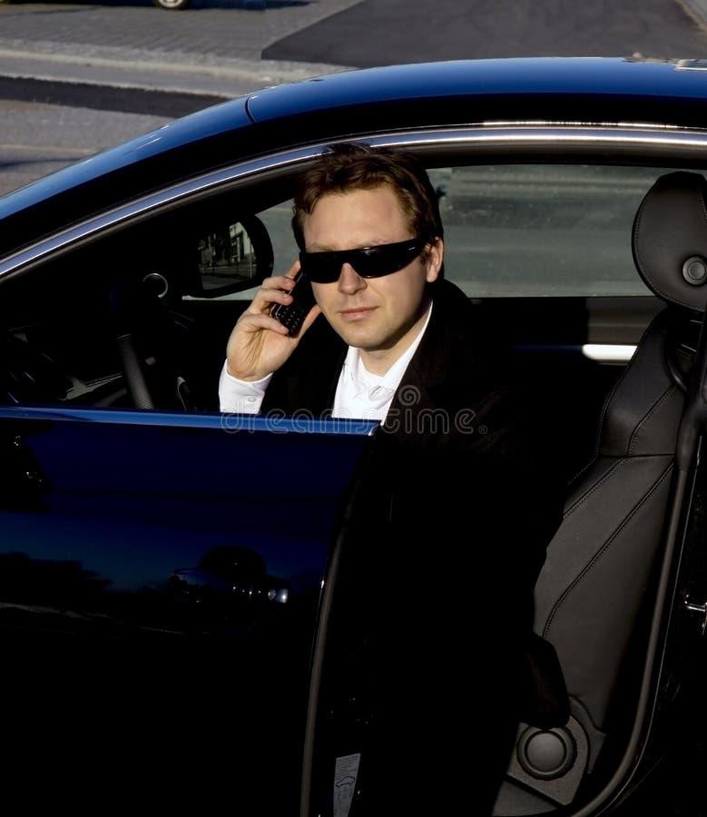 Geschäftsmannverlassen ein Auto stockbild