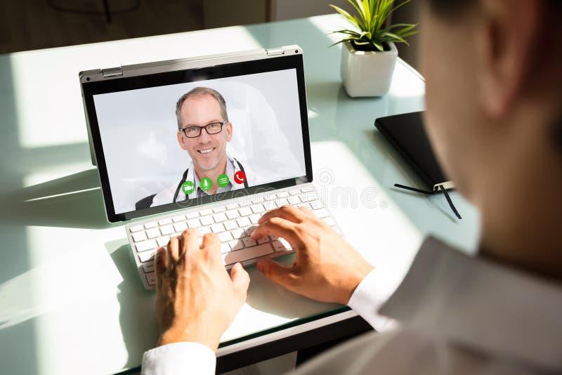 Geschäftsmannvideokonferenz mit Doktor auf Laptop lizenzfreie stockfotos