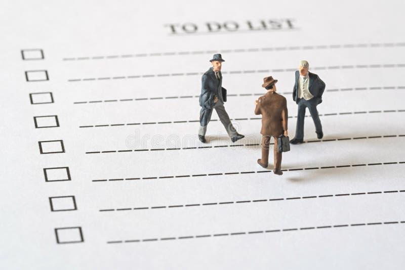 Geschäftsminiaturzahlen Leute, die an Liste tun gehen stockfoto