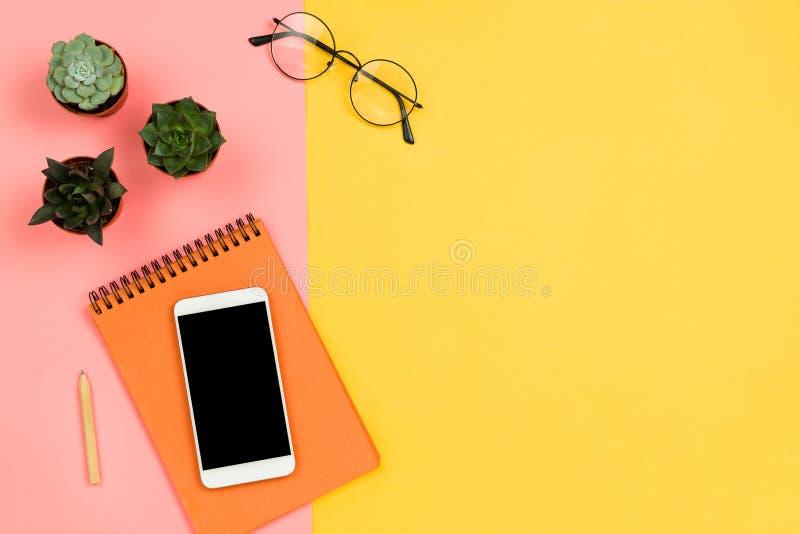 Geschäftsmodell mit Smartphone mit schwarzem copyspace Schirm, saftige Blumen, Gläser und Notizbuch, Pastellrosa und Gelb backg stockfotografie