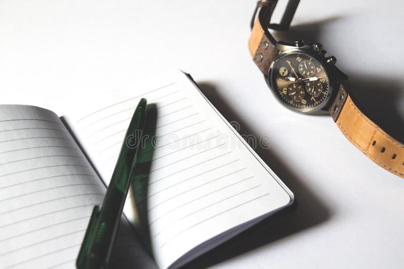 Geschäftsnotizbuch mit Stift und Uhr stockfotografie