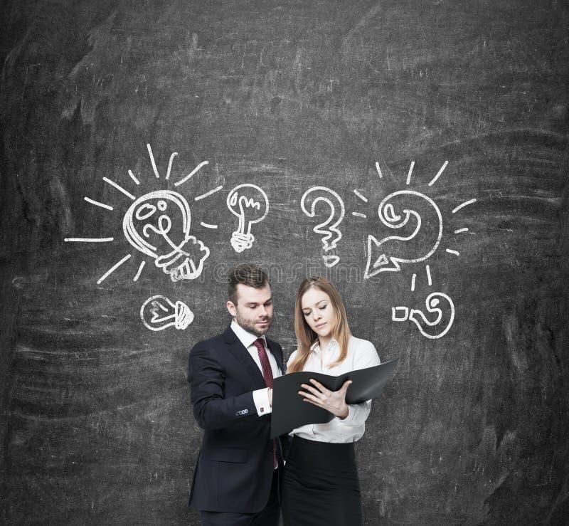 Geschäftspaare argumentieren über Geschäftsprojekt Ein Paar in der Abendtoilette halten einen schwarzen Dokumentenordner Glühlamp stockfotografie