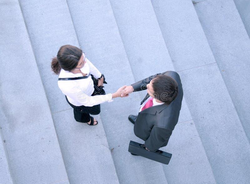 Geschäftspaare, die zusammen Hände rütteln lizenzfreie stockfotografie